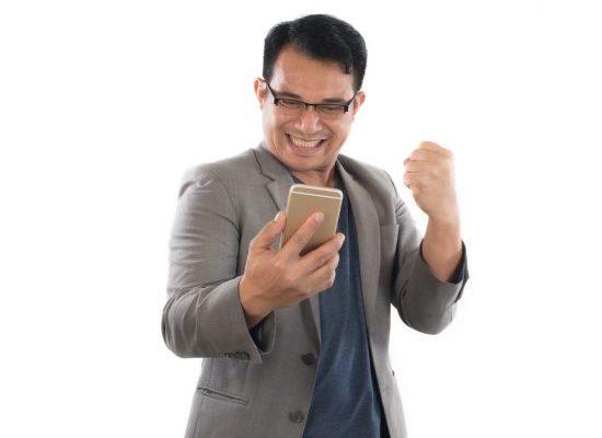 Mies tarkistaa kenotulokset tänään puhelimesta